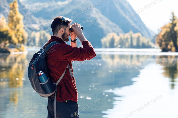 Hiker young man traveler with backpack looking the landscape with binoculars in the lake.