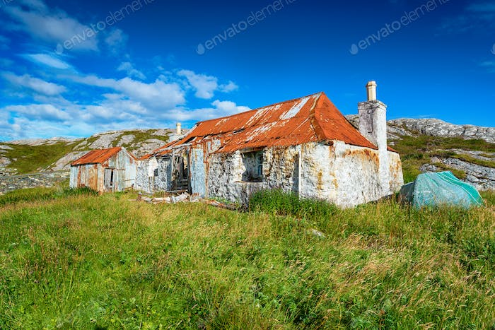 An old ruined croft with a rusty red tin roof at Quidnish