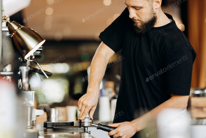 A stylish young man with beard,wearing casual clothes,cooks coffee in a coffee machine in a cozy