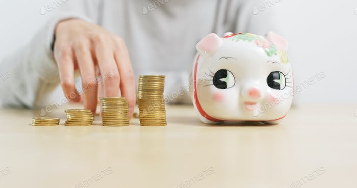 Woman putting coins into piggy bank