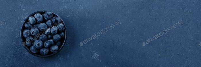 Schale mit Blaubeere auf klassischem blauem Hintergrund. Draufsicht. Kopierraum, Draufsicht. Banner für Website.