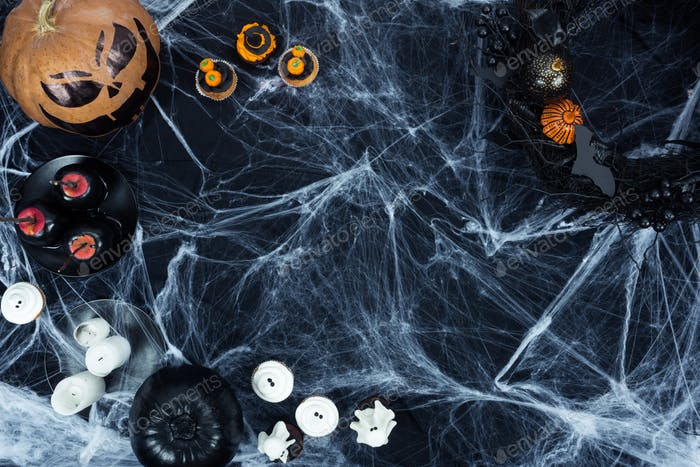 top view of delicious spooky halloween dessert and decorations in cobweb