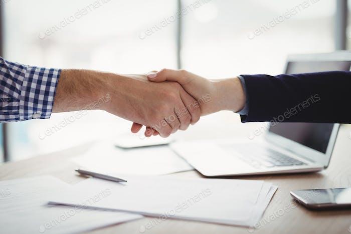 Close-up of executives shaking hands at desk