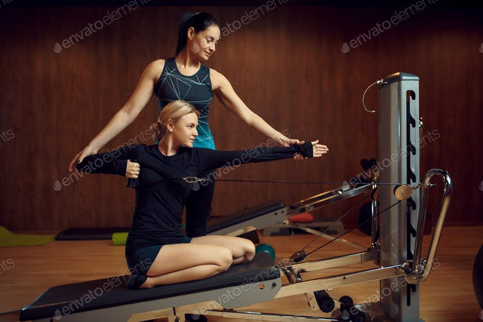 Slim woman on pilates training with instructor
