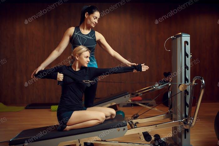 Schlanke Frau auf Pilates-Training mit Instruktor