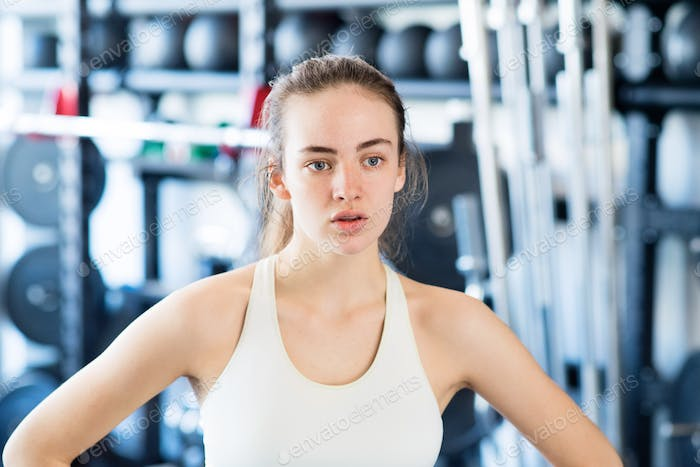 Young woman in gym, in white tank top, resting