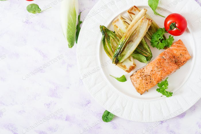 Baked salmon with Italian herbs and garnished with chicory. Top view