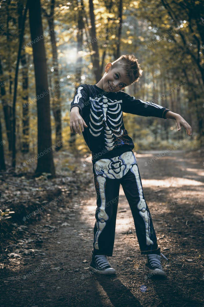 Young boy skeleton walking zombie in forest at halloween
