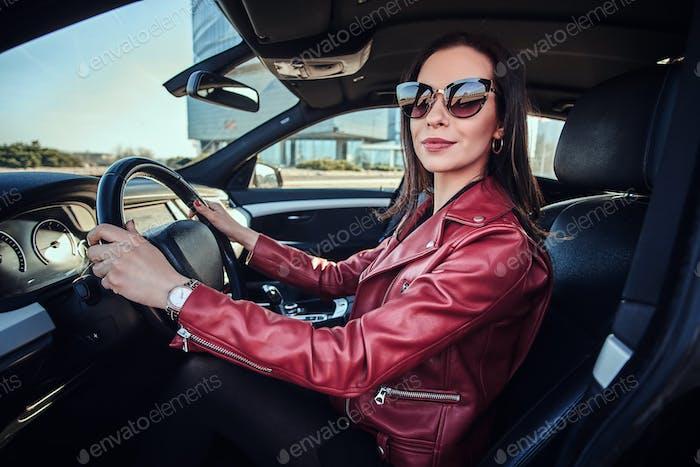 Attraktive junge Frau in roter Jacke und Sonnenbrille in ihrem Auto fahren