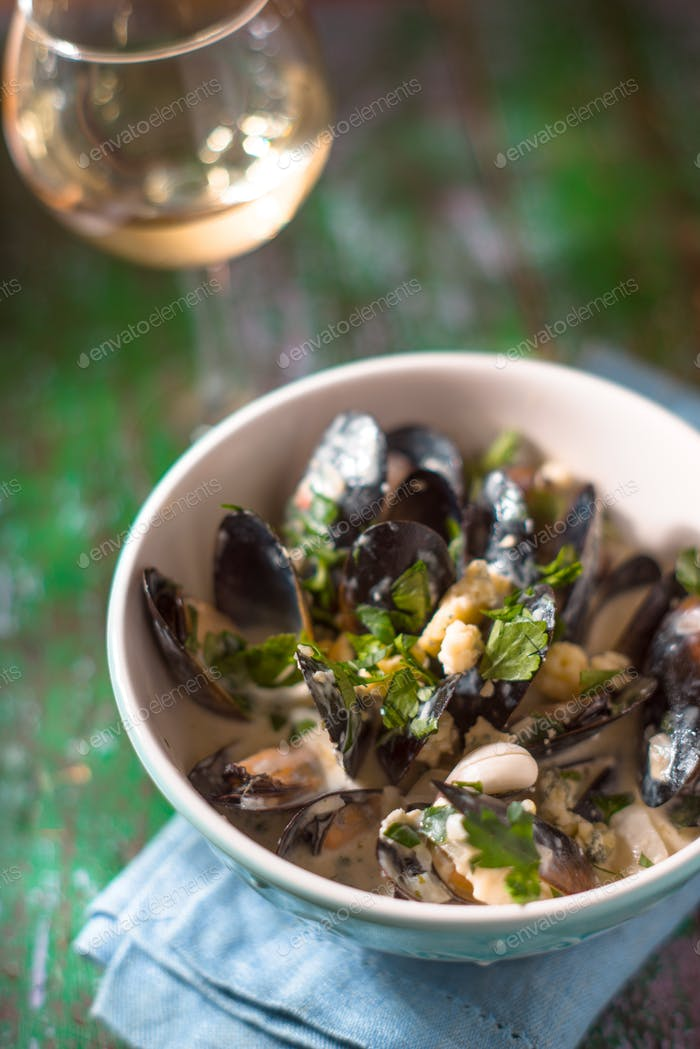 Mussels in Roquefort sauce on the blurred