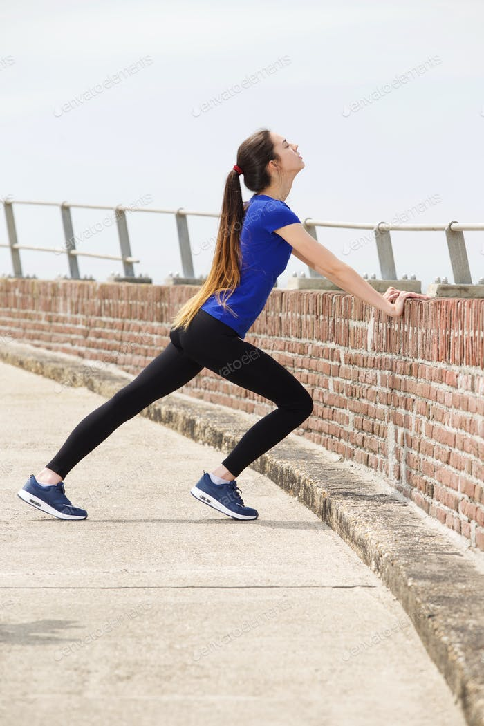 Attractive young female athlete in stretch outside