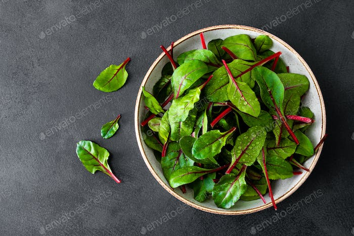 Fresh chard leaves on black background top view