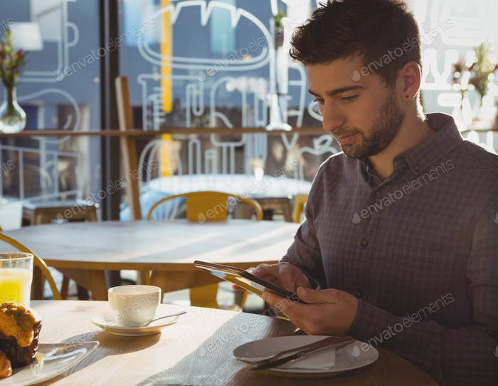 Businessman using tablet while having breakfast in cafe