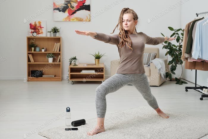 Pretty girl in activewear stretching legs and arms while working out on carpet