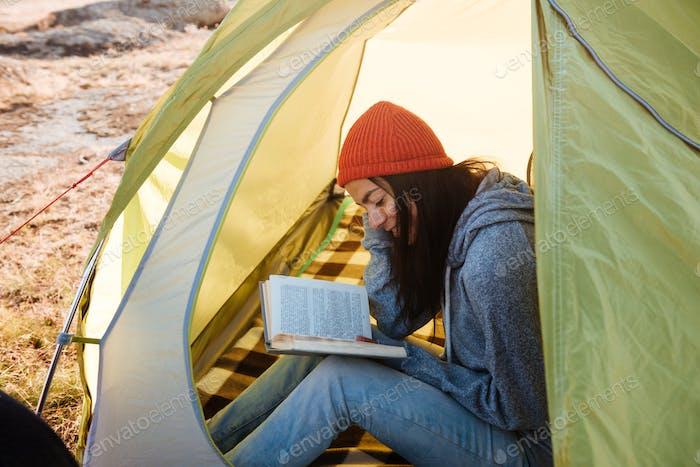 Frau mit Buch im Zelt
