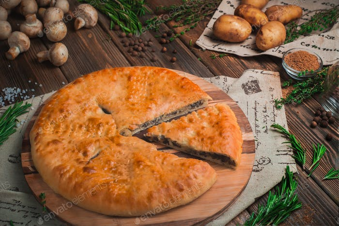 Potatoes and mushrooms pie on a wooden kitchen table with ingredients. Homemade baking concept
