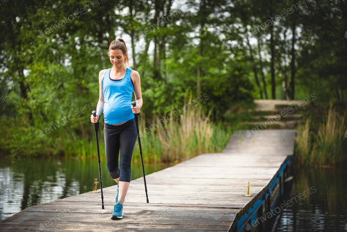 Pregnant woman nordic walking outdoor, exercises during pregnancy