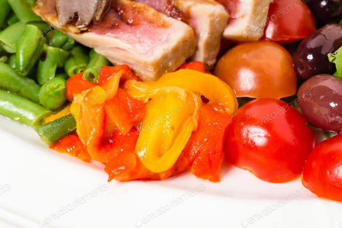 Delicious nicoise salad with tomatoes and olives.