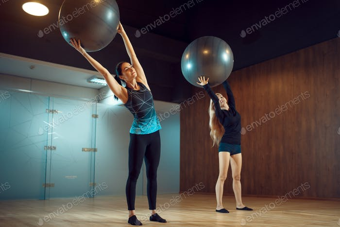Two women, pilates training with balls in gym