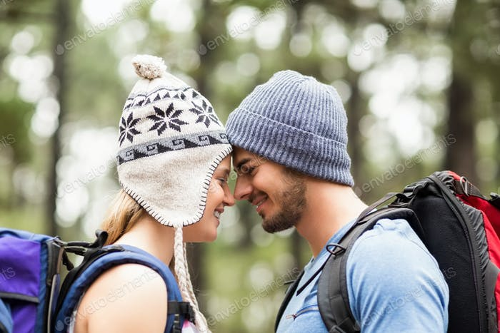 Young happy hiker couple touching foreheads in the nature