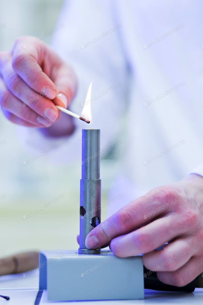 pretty, young female researcher lighting up a burner in a lab (s