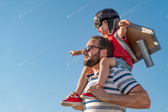 Father and son playing against blue summer sky background