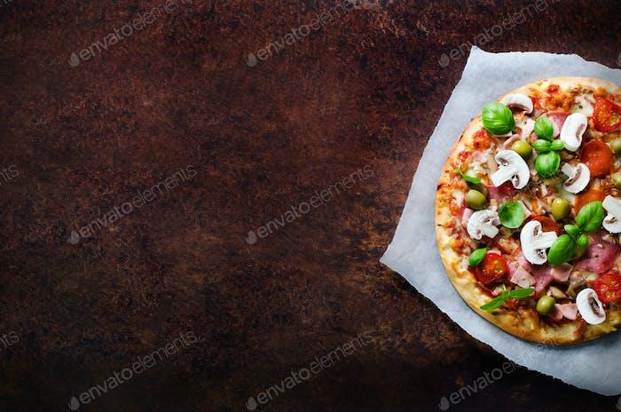Fresh italian pizza with mushrooms, ham, tomatoes, cheese, olive, basil, on backing paper, dark