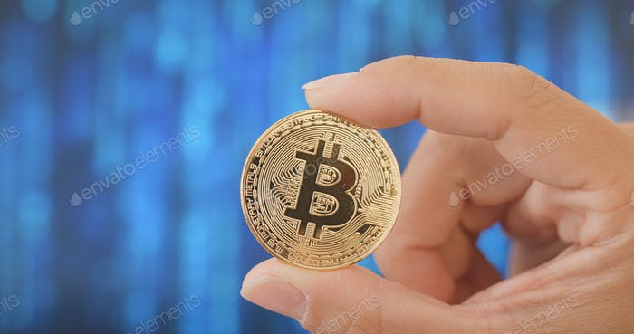 Mano sosteniendo bitcoin sobre fondo abstracto digital