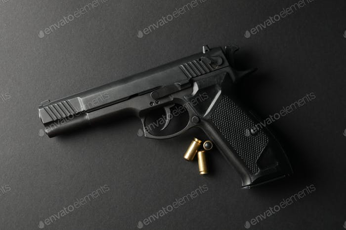 Pistol and traumatic bullets on black background. Self defense weapon