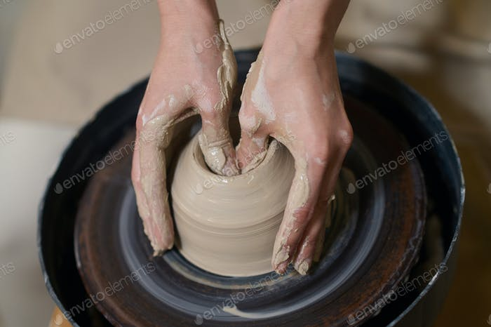 Close up of human hands on a pottery wheel
