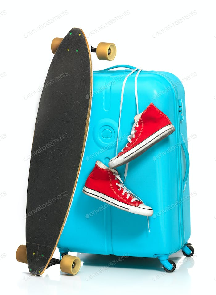 The blue suitcase, sneakers, skateboard on white background.