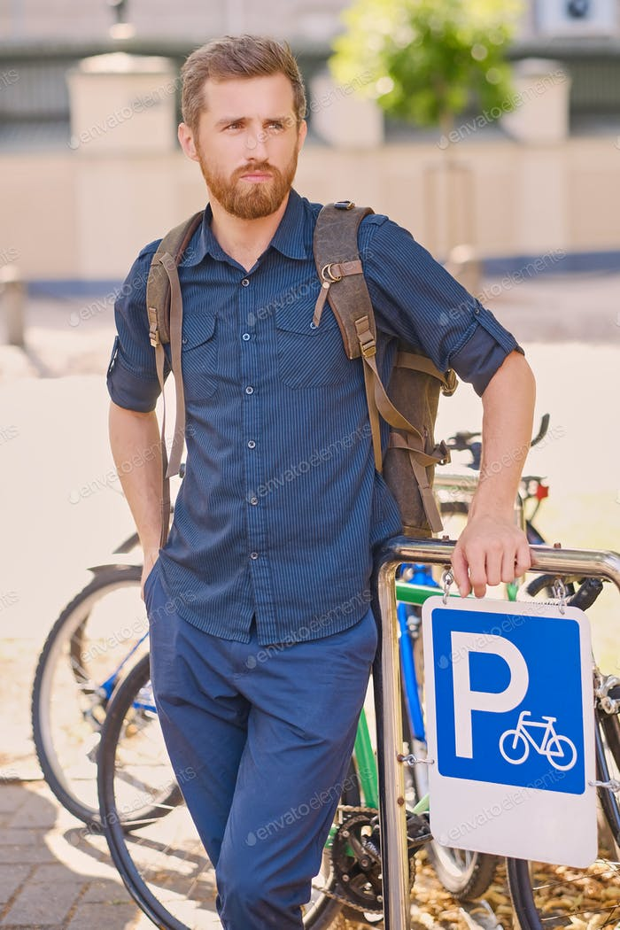 Man with smartphone near bicycles parking area.