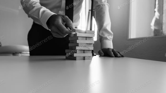 Businessman building a tower of stacked blocks of wood