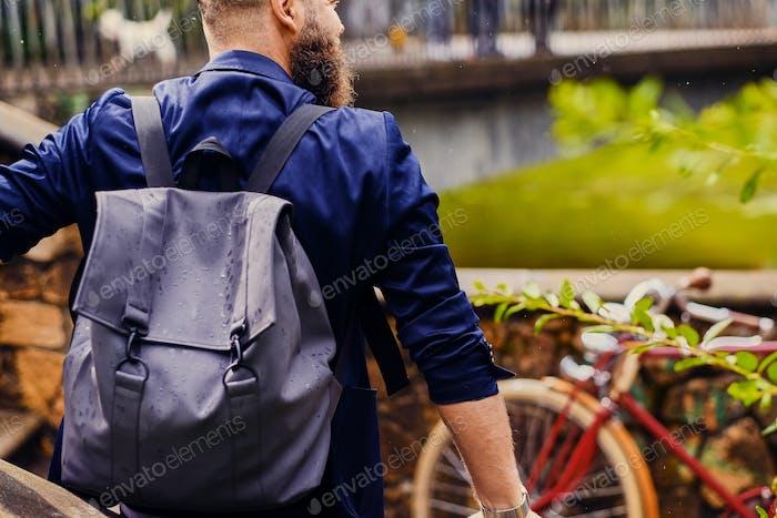 Hombre moderno con mochila. Vista trasera.