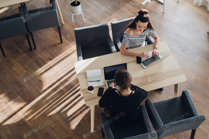 Overhead view of young woman wearing a smartwatch working on her laptop at a cafe. Top view shot of