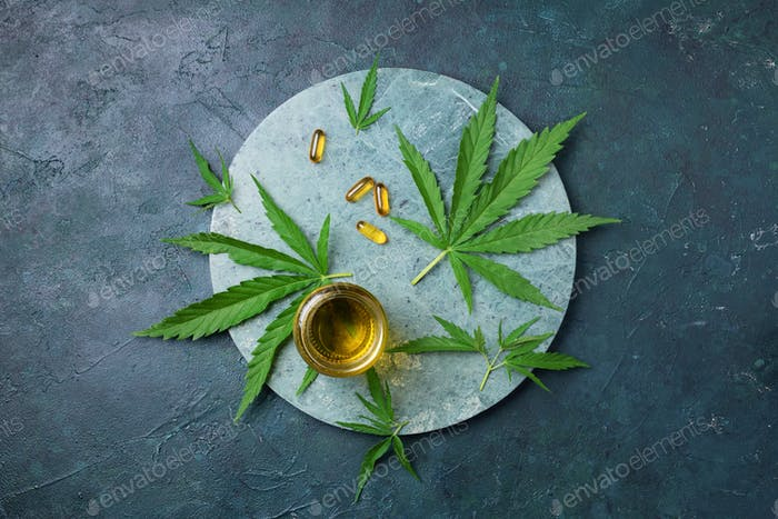 CBD oil, hemp oil capsules and cannabis leaves on dark background. Flat lay, copy space. Cosmetics
