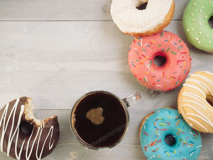 Donuts und Kaffee auf grauem Holzhintergrund, Kopierraum, Draufsicht