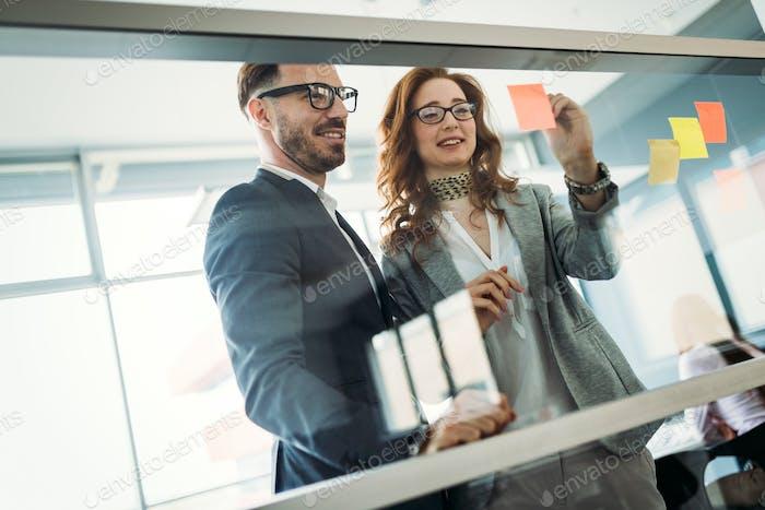 Geschäftsleute treffen sich im Büro und nutzen Post-Notizen, um Ideen zu teilen