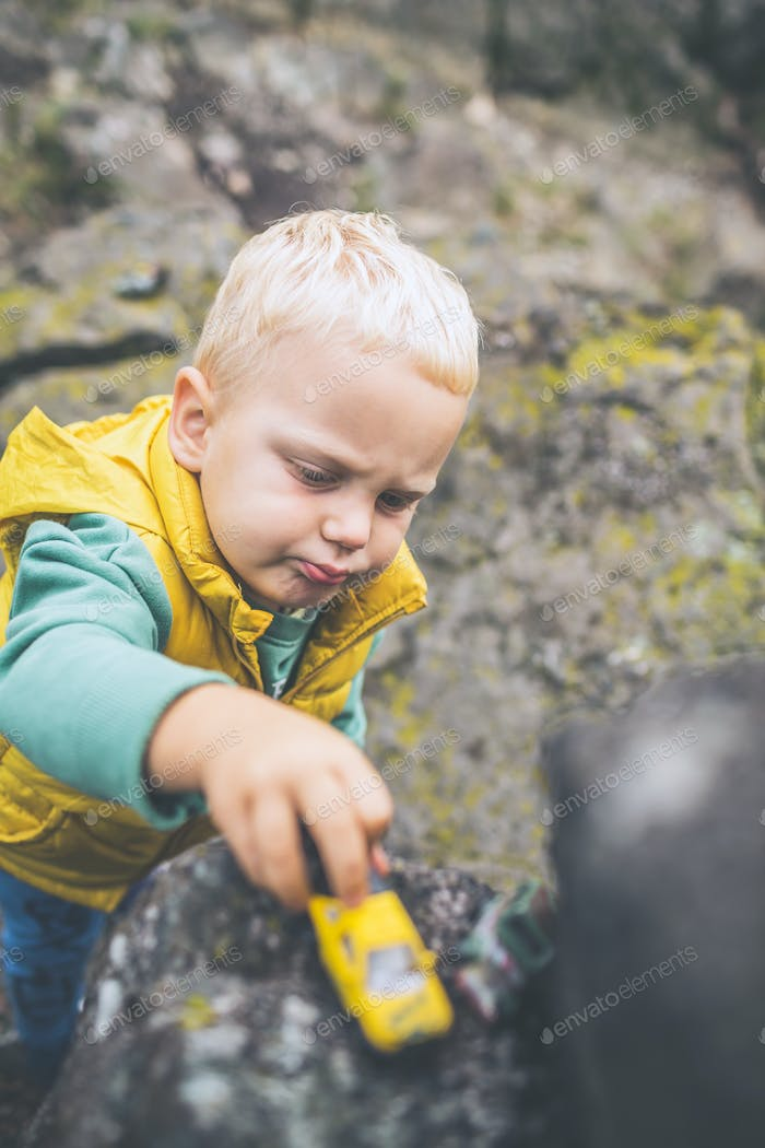 Toddler boy playing on a rock