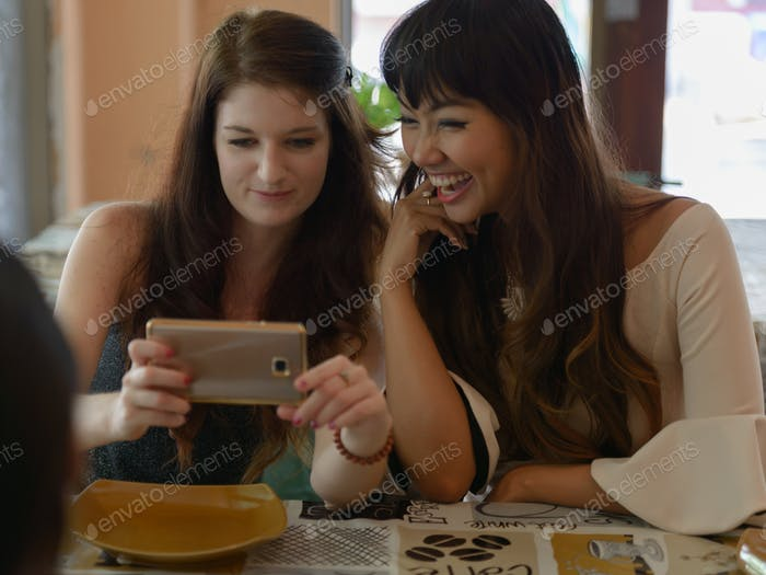 Three young beautiful women as friends together at the coffee shop