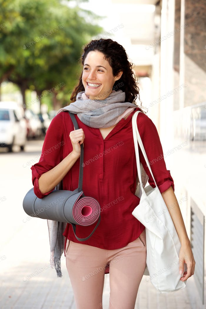 young woman smiling and walking to yoga lesson