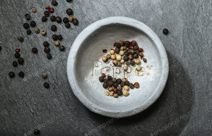 Black pepper in small bowl for spices on dark background. Bowl w