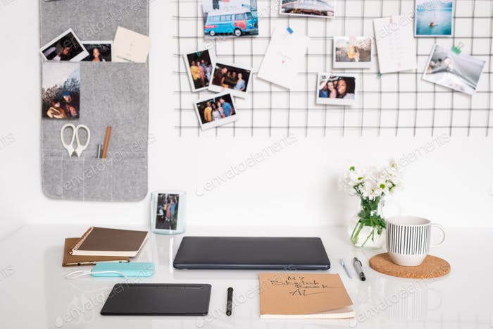 Workplace of designer by wall with folded laptop and other supplies on desk