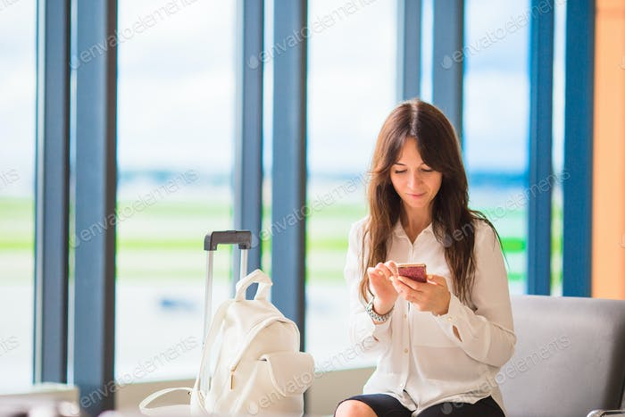 Female passenger in an airport lounge waiting for flight aircraft. Silhouette of woman with