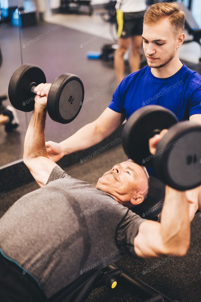 Personal trainer assisting older man in an exercise