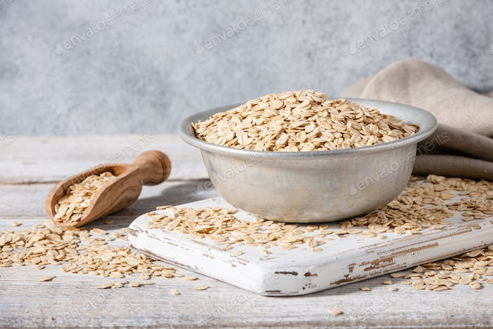 Dry oat flakes in vintage bowl on wooden table