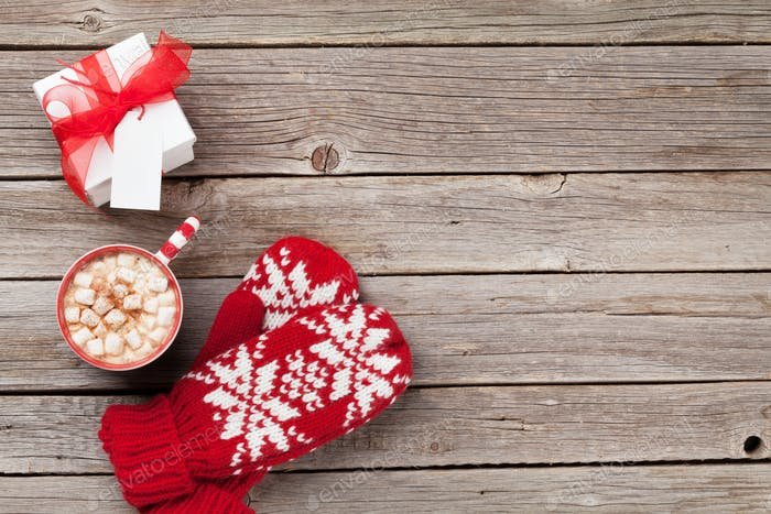 Christmas background with mittens, gift and hot chocolate