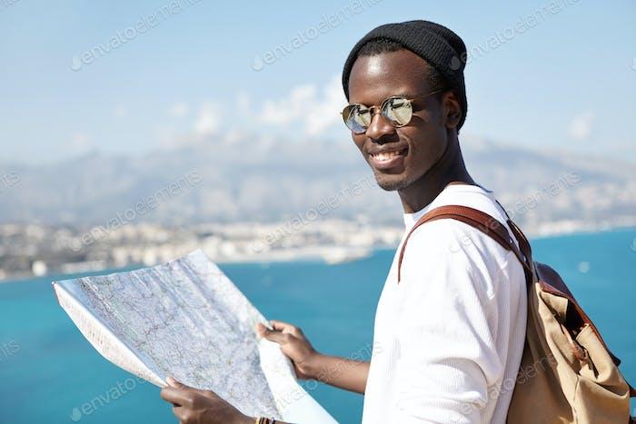 Disparo al aire libre de atractiva de moda de aspecto turístico de piel oscura estudio mapa de papel en sus manos, desgaste