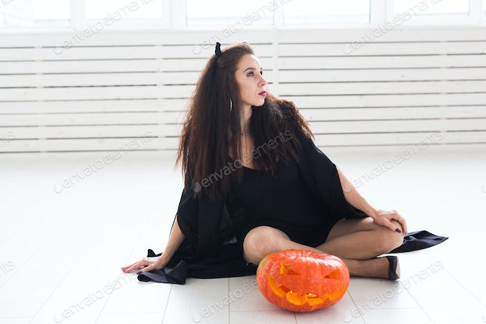 Smiling brunette woman in halloween makeup posing with carved pumpkin