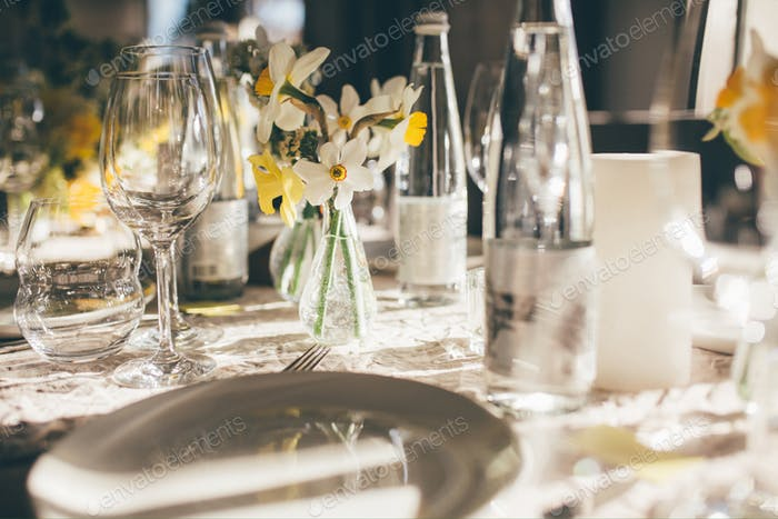 Table for guests, decorated with candles and flowers, served with cutlery and crockery